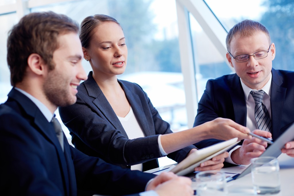 Group of confident business partners discussing paper at meeting